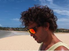 Un surfista che indossa un paio di occhiali da sole Out Of Swordfish in spiaggia