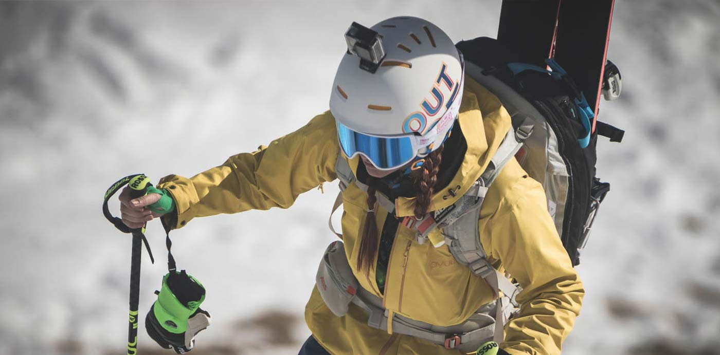 A freerider girl wearing an Out Of Shift ski goggle while climbing